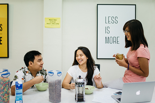 Ashley Uy smiling with other Self-taught managers at Symph