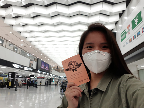 Ashley holding up her covid-negative certificate at Narita Airport
